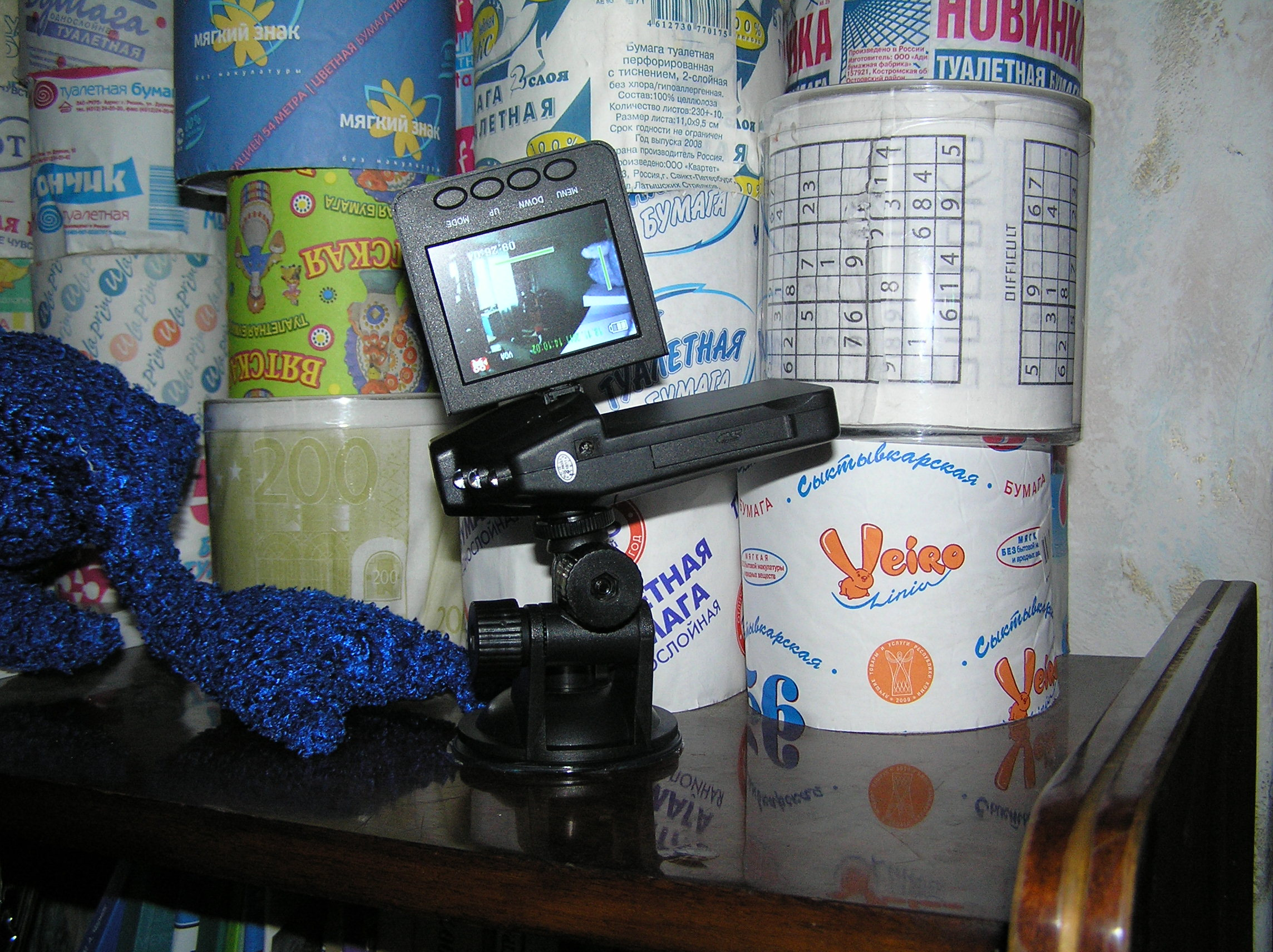 Автомобильный видеорегистратор в действии на фоне коллекции туалетной бумаги